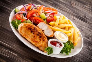 Fried chicken fillet, chips and vegetable salad