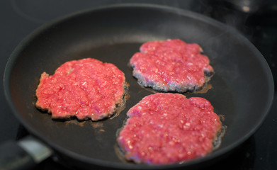 Ground beef patties in the pan.