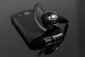 Close-up of handsfree bluetooth device near mobile phone.