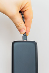 Male hand inserting micro USB to mobile phone.