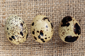 Three quail eggs on the jute background