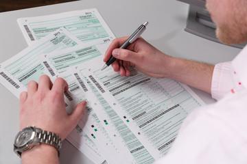 Junger Mann am Schreibtisch mit Formularen