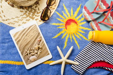 telo mare con accessori spiaggia e tablet