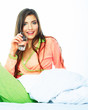 Smiling woman in bed hold water glass.