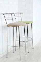 Bar high chairs on white brick wall background