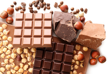 Chocolate bars with hazelnuts and coffee beans close up