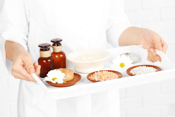 Beauty therapist holding tray of spa treatments, close-up