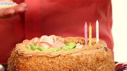 Baby handles decorate a cake with candles, inserting one by one