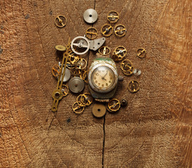 old watches and gears on wooden background