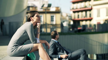 Young businesswoman relaxing while sitting on stairs in the city