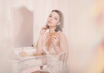 Sitting Young Woman in Nightdress Holding Perfume