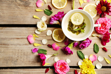Cup of herbal tea with beautiful flowers, on wooden background