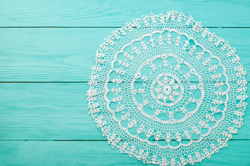 Lace doily on wooden background