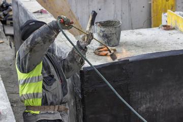 Insulation worker melting bitumen felt