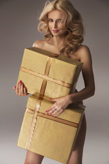 Seductive woman hiding her nude body behind gifts