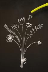 watering flowers on blackboard