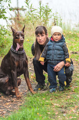 Young woman with her son and doberman dog on walk in autumn park