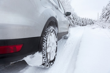Winter tyres wheels of car on snowy country road