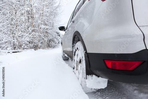 Staande foto Scandinavië Rear view of snow tires of car driving over snowdrift, winter