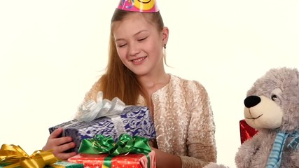 Girl in cap sitting at festive table and considers all their