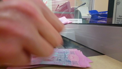 Male hands counting paper money, making payment at bank