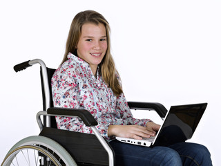 Girl sat in a wheelchair with a portable computer