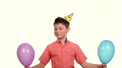 boy holding a two balloons and releasing them into the air, they