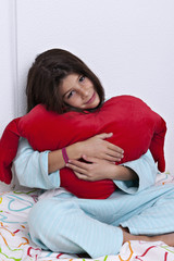Girl embracing big soft red heart