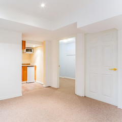 Empty basement living room with kitchen design