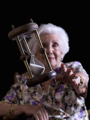 Elderly Woman trying to get an hourglass.Trapping time