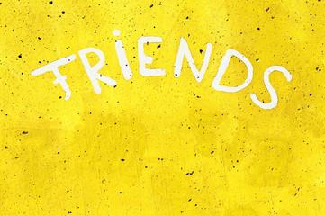 Aufschrift - Friends - auf einer Wand in Knall-Gelb