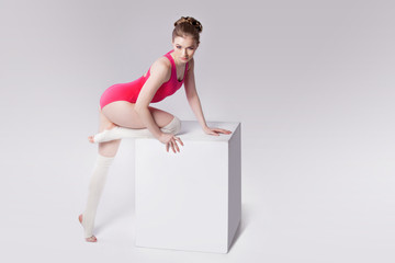 attractive young woman gymnast on a white cube, place for text