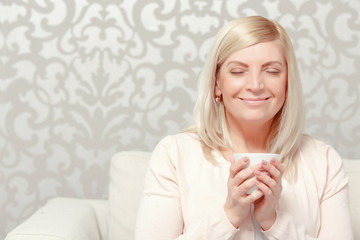 Woman drinks tea on the sofa