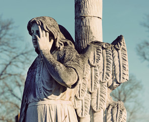 The old stone statue of an angel headstone in the cemetery in vi