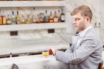 Young man sits at the counter of bar