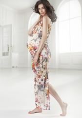 Brunette pregnant woman wearing flowered dress