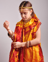 girl putting on traditional Indian clothing and jeweleries