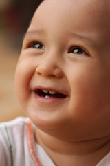 Extreme close up of infant's face smiling, showing growing teeth