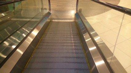 Escalator slowly moving down, reaching end, shopping mall