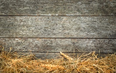 Straw and wheat on a rustic wooden background with copy space