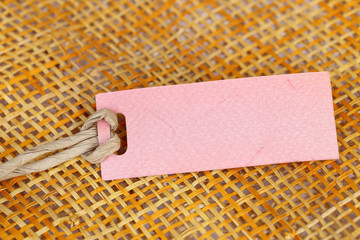 Paper tag blank for text on bamboo weave background.