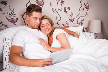junges Pärchen im Bett beim lesen auf dem Tablet