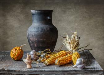 Темный глиняный кувшин, пучок кукурузы и свисток.