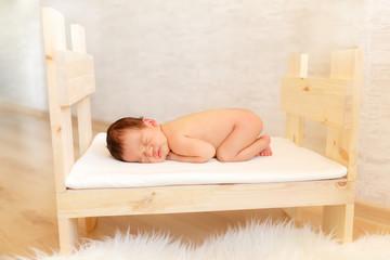 newborn baby sleeping in a baby cot