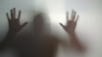 Silhouette of mad man against wall, schizophrenia, addiction