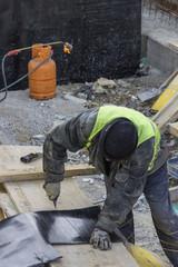 Insulation worker preparing bitumen felt 2
