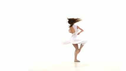 Young and slim woman in light dress dancing contemp jazz modern
