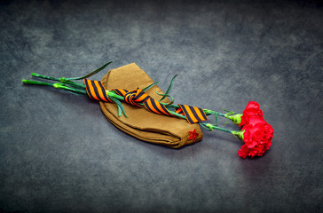 Carnation flowers, George Ribbon and military garrison cap