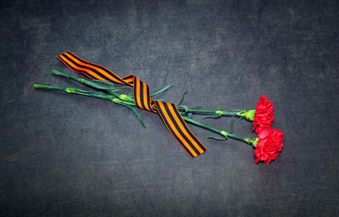 Carnations and St. George ribbon on a dark background