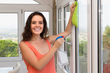Positive woman cleaning windows in house